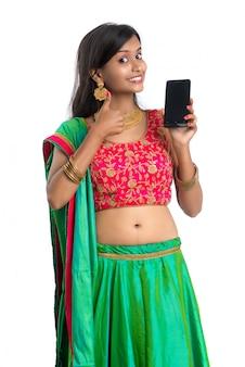 Joven india tradicional utilizando un teléfono móvil o teléfono inteligente y mostrando el teléfono inteligente de pantalla en blanco sobre superficie blanca