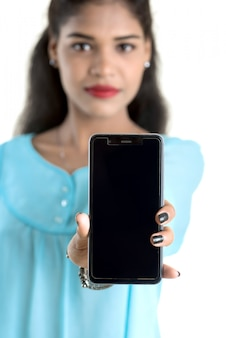Joven india usando un teléfono móvil o teléfono inteligente aislado en una pared blanca