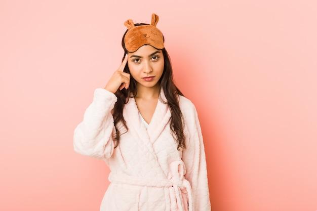 Joven india vistiendo un pijama y antifaz para dormir apuntando a algo en su sien con el dedo, pensando, centrado en una tarea.