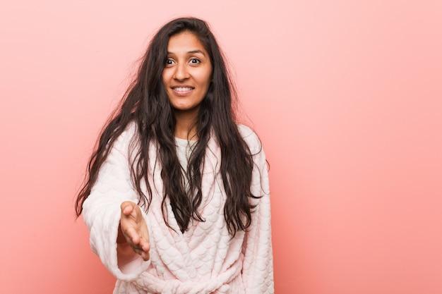 Joven india vistiendo pijama estirando la mano a la cámara en gesto de saludo