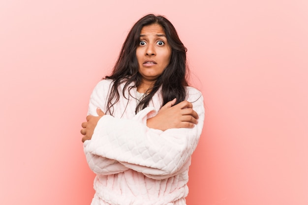 Joven india vistiendo pijama va frío debido a la baja temperatura o una enfermedad.