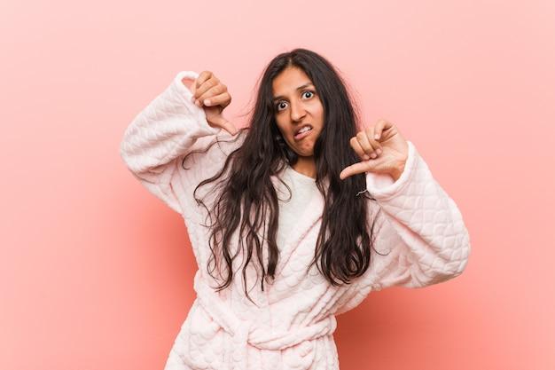 Joven india vistiendo pijama mostrando el pulgar hacia abajo y expresando aversión.