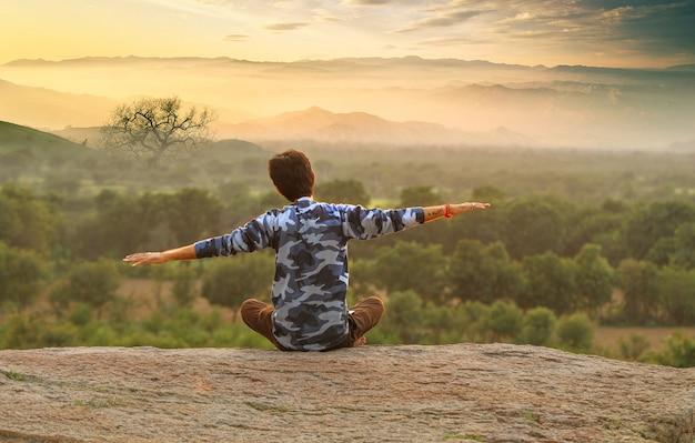 Joven indio en la cima de la montaña sentado en pose de yoga.