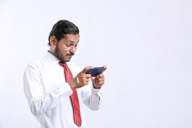 Joven indio dando expresión impactante después de ver el teléfono inteligente.