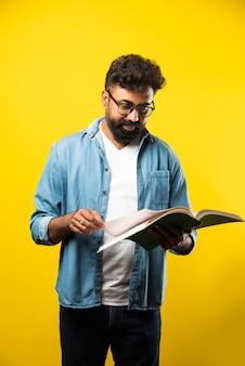 Joven indio feliz con anteojos leyendo el libro y sonriendo aislado en amarillo