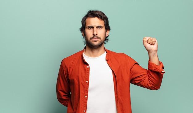 Joven indio guapo que se siente serio, fuerte y rebelde, levantando el puño, protestando o luchando por la revolución