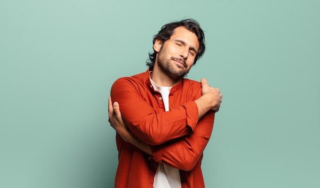 Joven indio guapo sintiéndose enamorado, sonriendo, abrazándose y abrazándose a sí mismo, permaneciendo soltero, siendo egoísta y egocéntrico