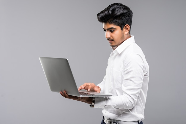 Joven indio con laptop en pared gris