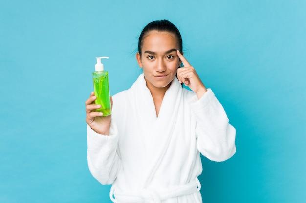 Joven indio de raza mixta sosteniendo una botella de aloe vera apuntando su sien con el dedo, pensando, centrado en la tarea.