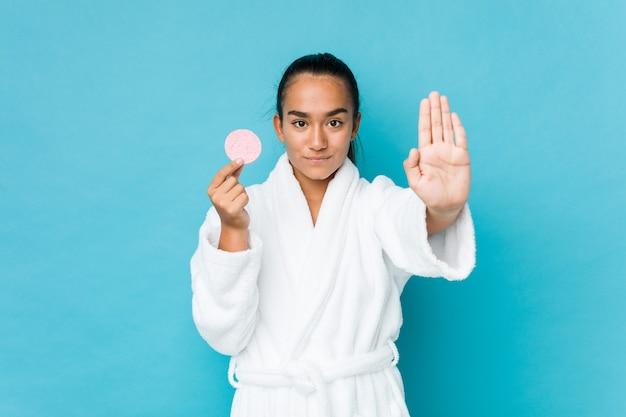 Joven indio de raza mixta sosteniendo una esponja facial de pie con la mano extendida que muestra la señal de stop, impidiéndole.