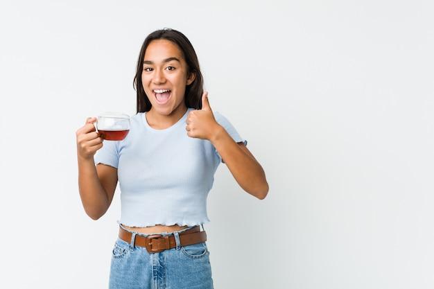 Joven indio de raza mixta sosteniendo una taza de té sonriendo y levantando el pulgar