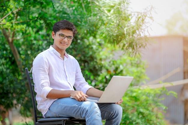 Joven indio usando laptop, trabajando en laptop