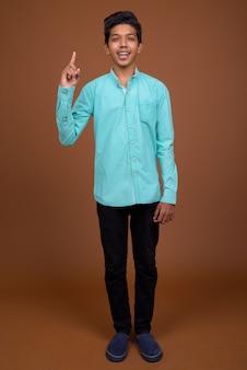 Joven indio vistiendo camisa azul mirando inteligente contra el fondo marrón