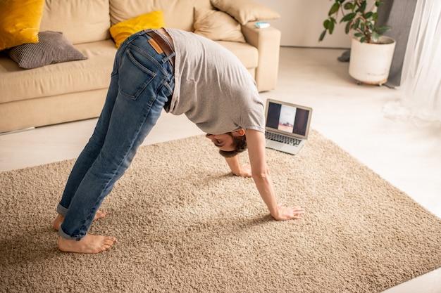 Joven inflexible en jeans practicando pose de perro boca abajo con entrenador en línea durante el aislamiento doméstico