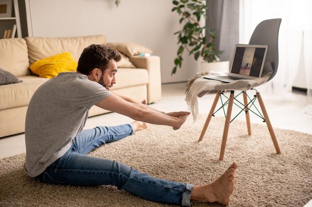 Joven inflexible en ropa casual sentado en la alfombra y practicando gran angular sentado inclinado hacia adelante mientras ve la clase de yoga en línea