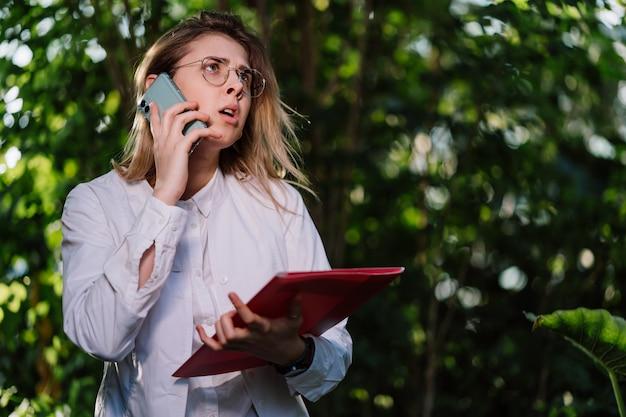 Joven ingeniera agrícola hace una llamada en invernadero.