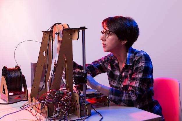 Joven ingeniera diseñadora usando una impresora en el laboratorio y estudiando un concepto de prototipo de producto, tecnología e innovación.