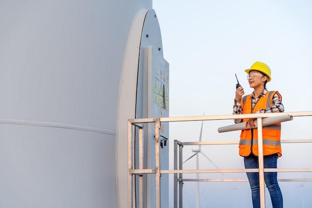 Joven ingeniera con walkie talkie para comprobar el sistema contra la granja de turbinas eólicas