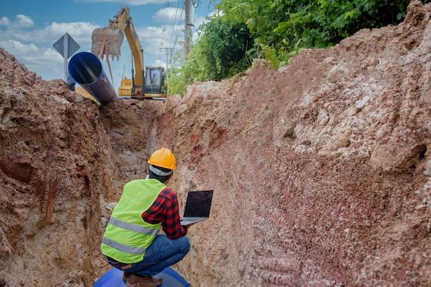 Un joven ingeniero asiático está inspeccionando una gran alcantarilla que está enterrada bajo tierra en un sitio de construcción