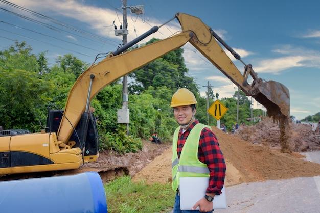 Un joven ingeniero asiático está inspeccionando una gran alcantarilla en el sitio de construcción