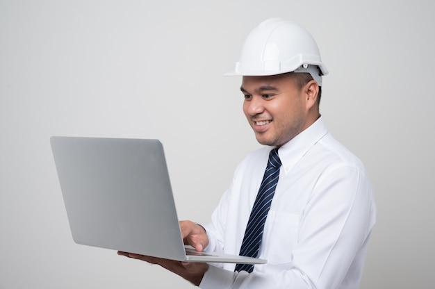 Joven ingeniero civil asiático guapo con un portátil