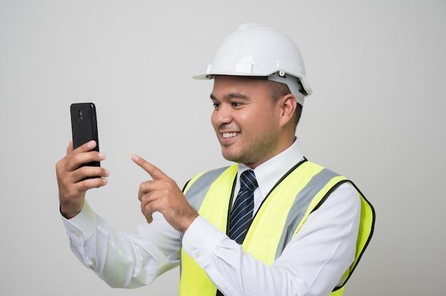 Joven ingeniero civil asiático guapo con un teléfono
