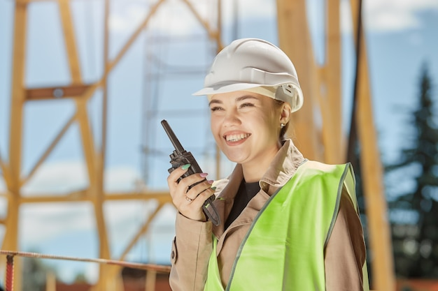 Joven ingeniero civil en la construcción de edificios se comunica por walkie con una sonrisa en su rostro