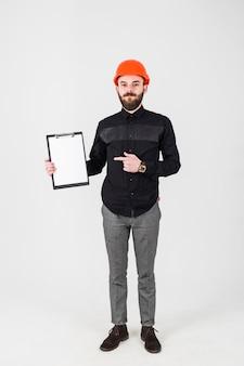 Joven ingeniero civil masculino con gesticular portapapeles