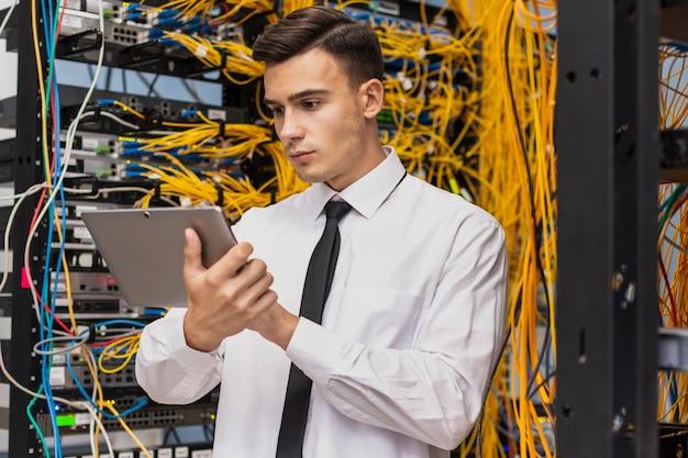 Joven ingeniero comercial en una sala de servidores de red