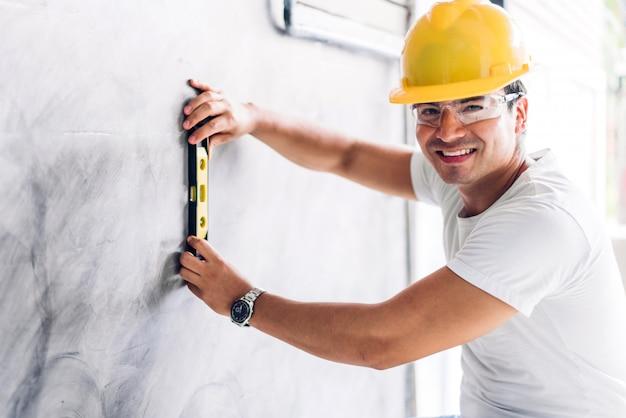 Joven ingeniero de construcción en un casco amarillo trabajando y haciendo mediciones en la pared en el sitio de construcción