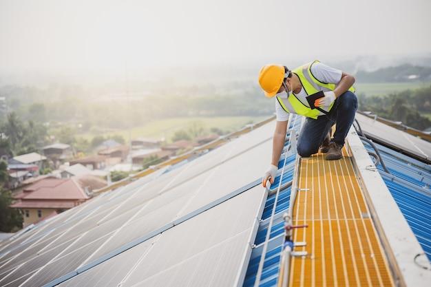 Joven ingeniero eléctrico trabajar en una planta de energía fotovoltaica verificar la calidad del panel solar y controlar la electricidad en el edificio por un técnico en sistemas fotovoltaicos