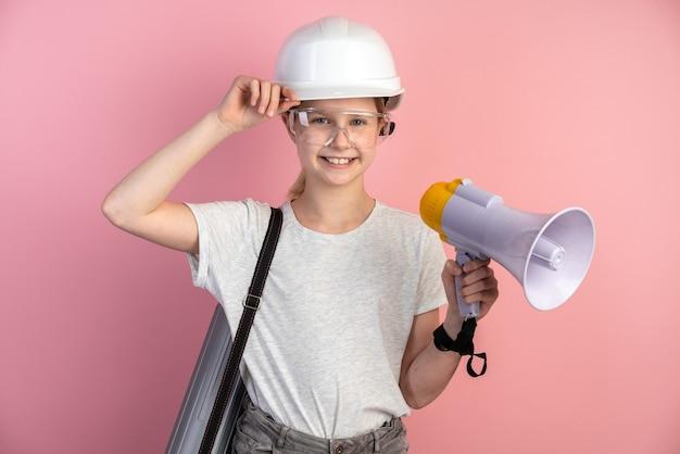 Joven ingeniero es una niña en una pared de una pared rosa, con un casco, gafas y un altavoz en sus manos