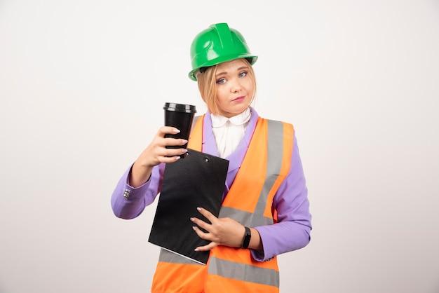 Joven ingeniero industrial en uniforme con portapapeles y taza negra sobre pared blanca.