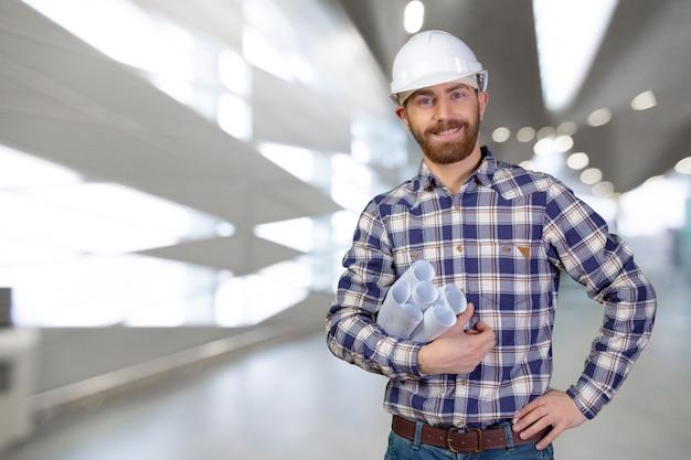 Joven ingeniero masculino con casco con planos