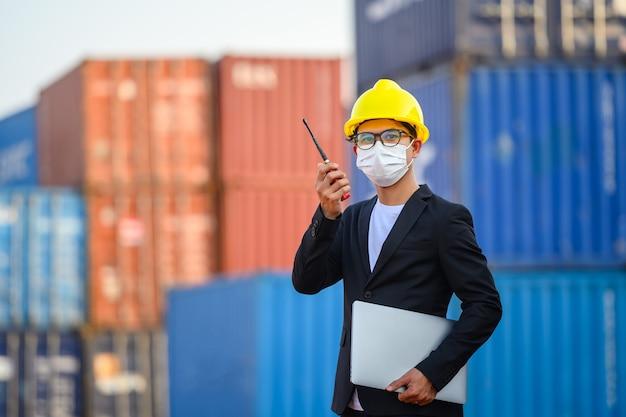 Joven ingeniero o gerente de sexo masculino asiático uso de comunicaciones por radio y computadoras portátiles para controlar la carga de contenedores en conceptos de transporte industrial y logística.