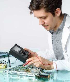 Joven ingeniero o ingeniero masculino enérgico repara equipos electrónicos