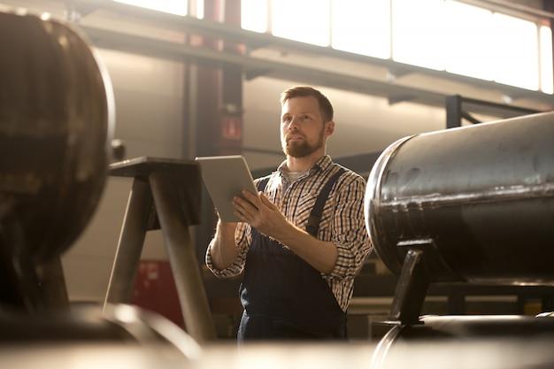 Joven ingeniero o técnico barbudo en ropa de trabajo desplazándose en el panel táctil mientras está de pie entre máquinas industriales
