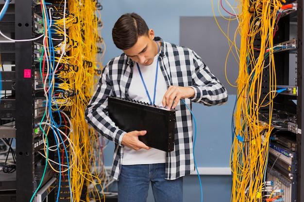 Joven ingeniero de redes con conmutadores ethernet