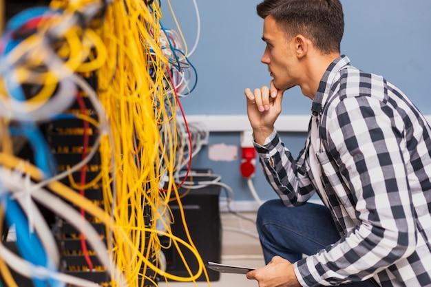 Joven ingeniero de redes mirando cables