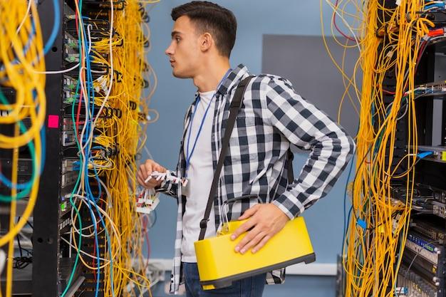 Joven ingeniero de redes mirando conmutadores ethernet