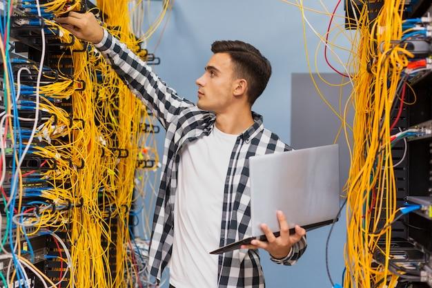 Joven ingeniero de redes en la sala de servidores con una computadora portátil