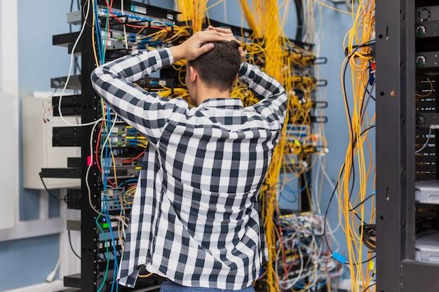 Joven ingeniero de redes en sala de servidores