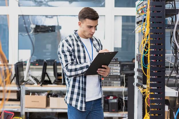 Joven ingeniero trabajando en sala de servidores