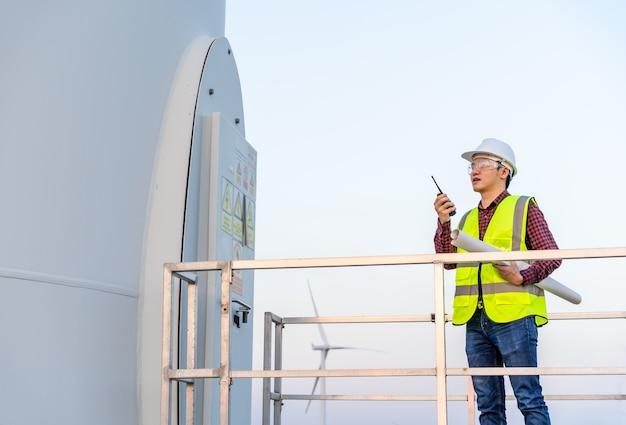 Joven ingeniero con walkie talkie para comprobar el sistema contra la granja de turbinas eólicas