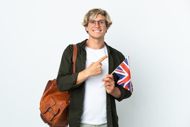 Joven inglesa sosteniendo una bandera del reino unido apuntando hacia el lado para presentar un producto
