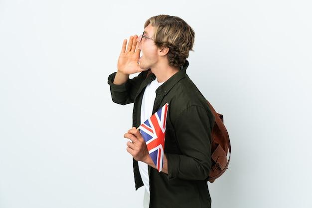 Joven inglesa sosteniendo una bandera del reino unido gritando con la boca abierta hacia el lado