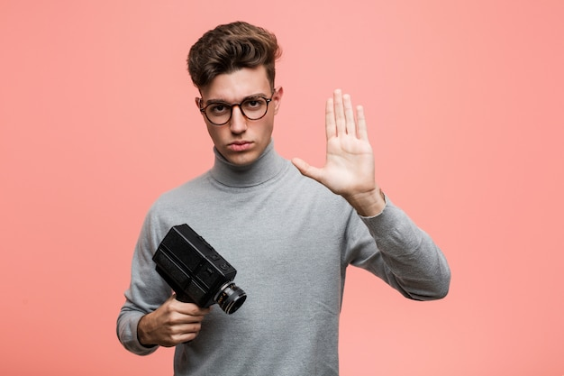 Joven intelectual sosteniendo una cámara de cine de pie con la mano extendida que muestra la señal de stop, impidiéndole.