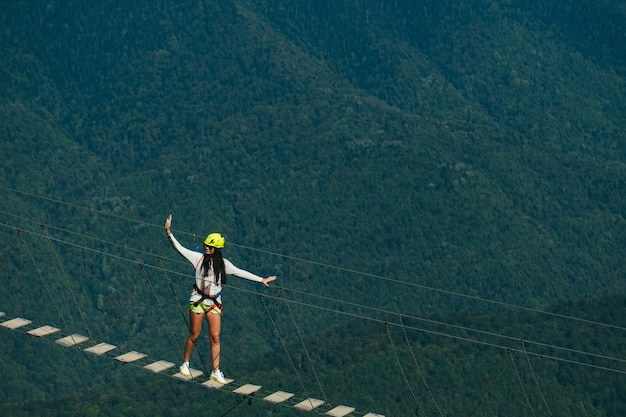 Una joven intrépida camina sobre un puente de cuerda sobre un precipicio en lo alto de las montañas