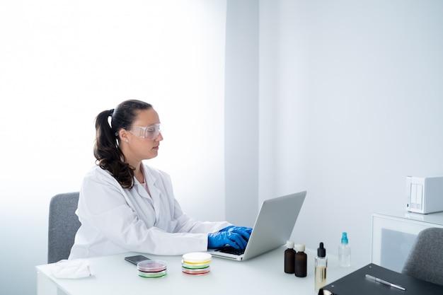 Joven investigadora o científica en bata blanca y guantes azules está escribiendo en una computadora portátil en un laboratorio