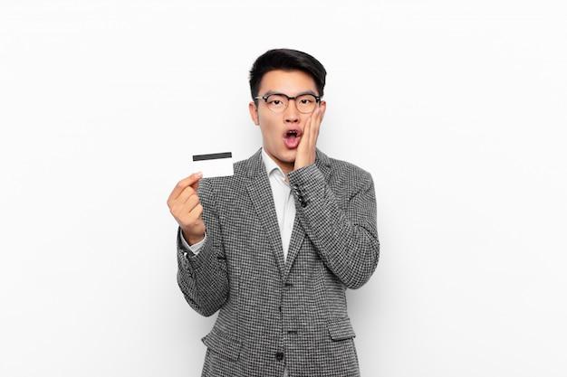 Joven japonés se siente conmocionado y asustado, mirando aterrorizado con la boca abierta y las manos en las mejillas. concepto de tarjeta de crédito